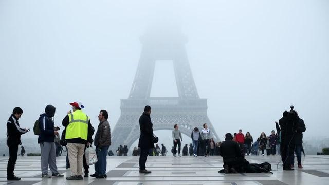 Menschen, einer mit Gelbweste, vor dem Eiffelturm