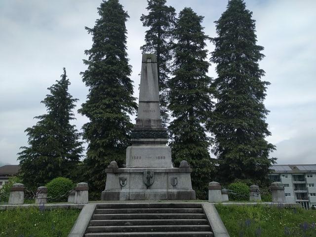 steiniges Denkmal in der Wiese neben Bäumen.