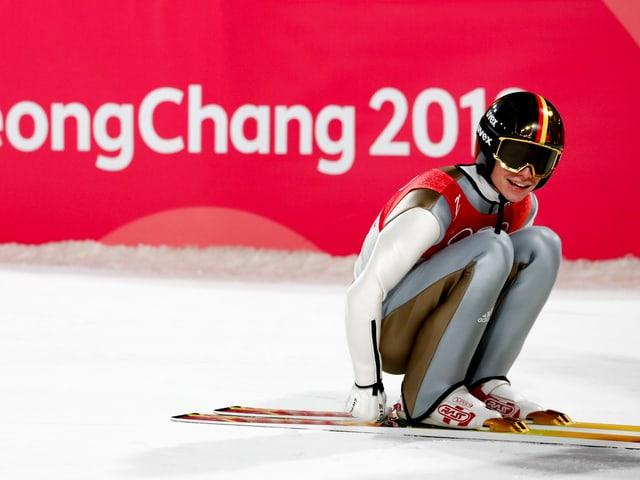 Andreas Wellinger schnallt sich die Skier ab.