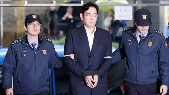 Der designierte Konzernchef in Handschellen, links und rechts zwei Polizisten.