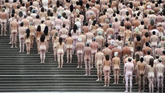 Das Bild zeigt vollkommen nackte Menschen von hinten, die nebeneinander und hintereinander auf Treppenstufen des Opernhauses in Sidney aufgereiht sind.