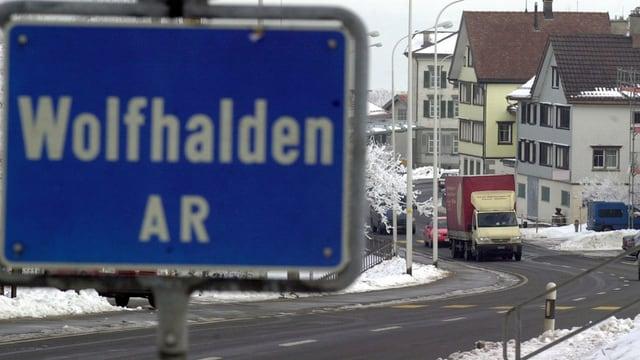 Das Ortsschild von Wolfhalden im Vordergrund, im Hintergrund eine Strasse.