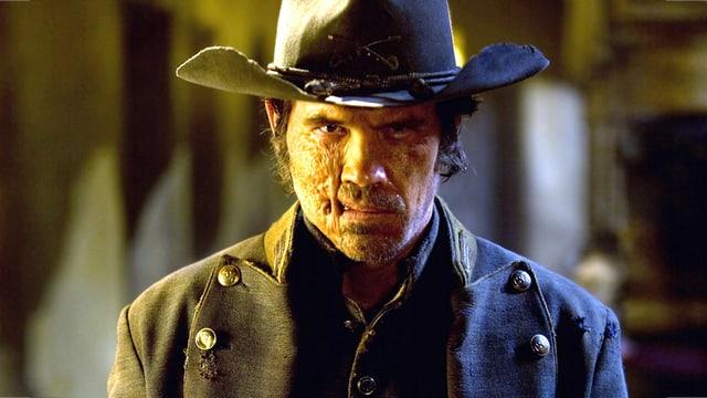 Ein Mann mit Cowboyhut und Narbe im Gesicht.