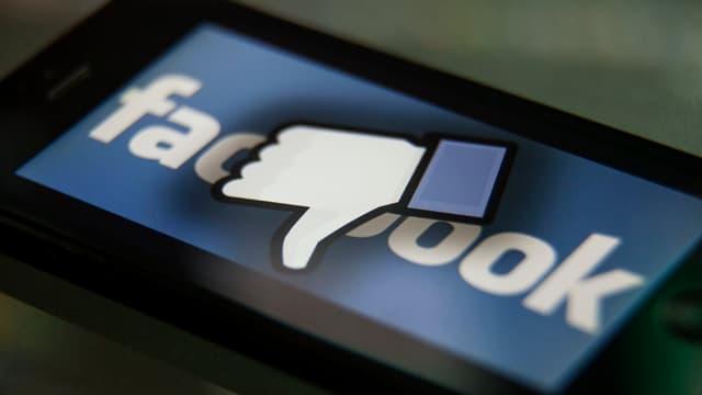 Ein Screen mit einem Facebook-Logo. Auf dem Logo ist ein Daumen, der nach unten zeigt.