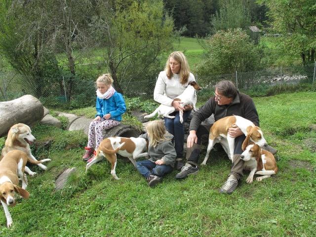 Zwei Kinder und zwei Erwachsene mit vier Hunden