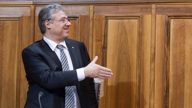 Filippo Lombardi reicht jemandem die Hand.