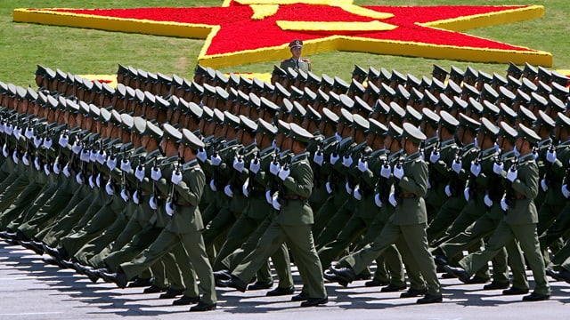 Im Gleichschritt marschieren hunderte chinesische Soldaten mit dem Gewehr im Anschlag. Im Hintergrund das Logo der Volksbefreiungsarmee.