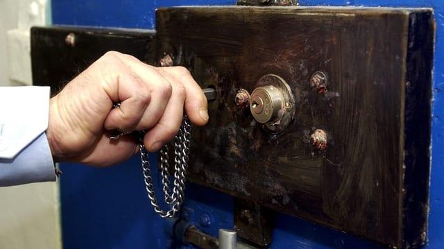 Gefängniswärter schliesst Türe einer Zelle