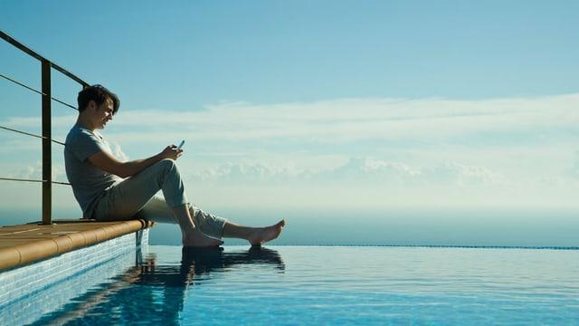 Ein Mann sitzt an einem Pool mit dem Handy in der Hand.