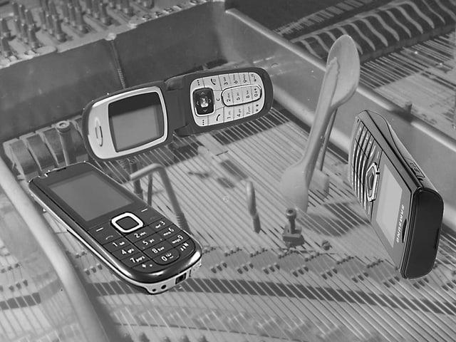 Handys (ältere Modelle) liegen im Klangkasten eines Pianos auf den Saiten.
