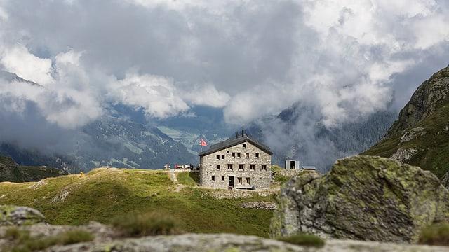 Eine Berghütte auf einem Grat, im Hintergrund Wolken.