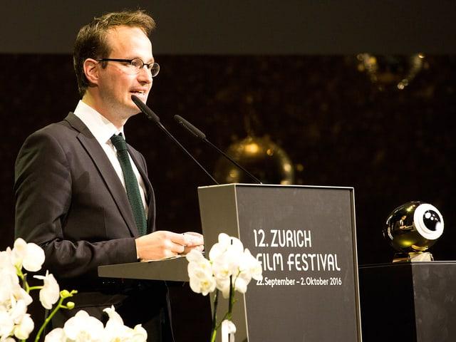 Der Regisseur steht am Rednerpult. Weisse Blumen und der Preis - ein goldenes Auge - umrahmen in.