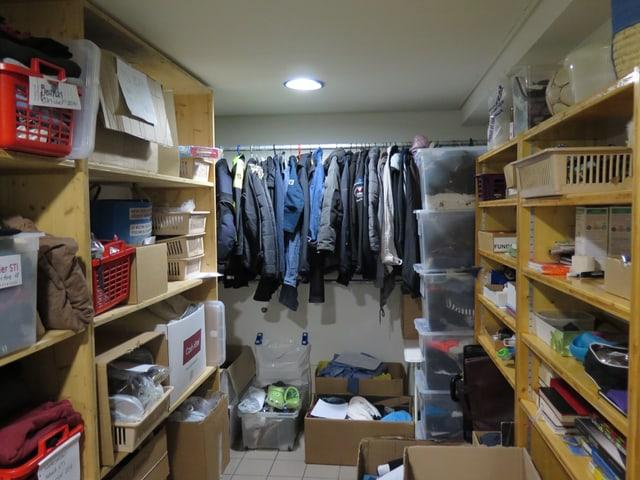 Holzregale mit vielen Kisten und Boxen, im Hintergrund eine Kleiderstange.