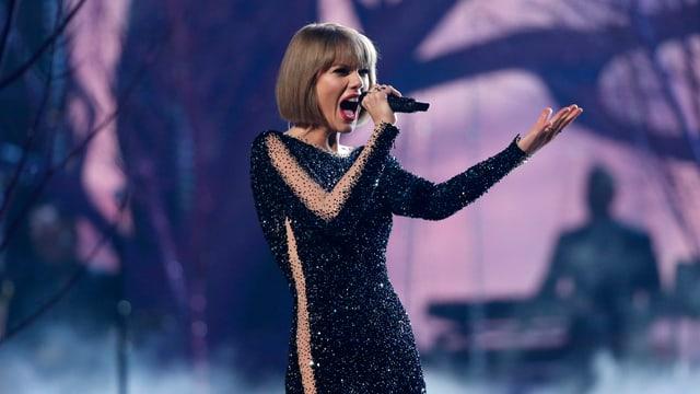Taylor Swift singt in ein Mikrofon, im Hintergrund ein Bühnenbild mit Abbildung von Bäumen.