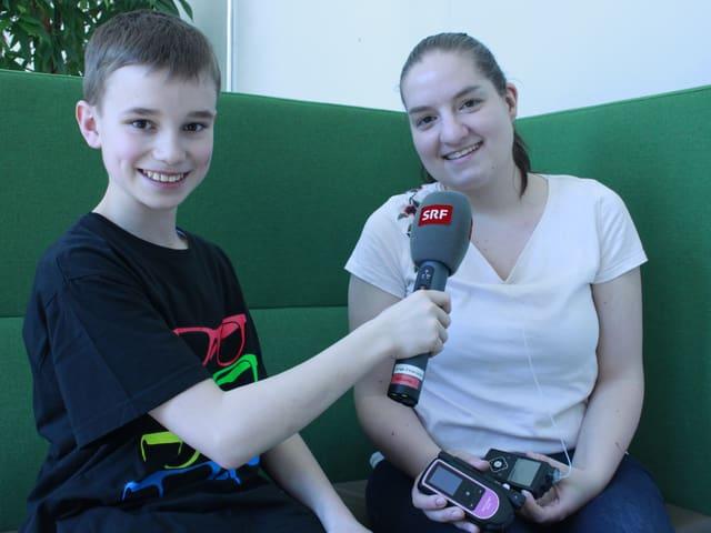 Der Junge Micha führt ein Interview mit Reporterin Giulia.