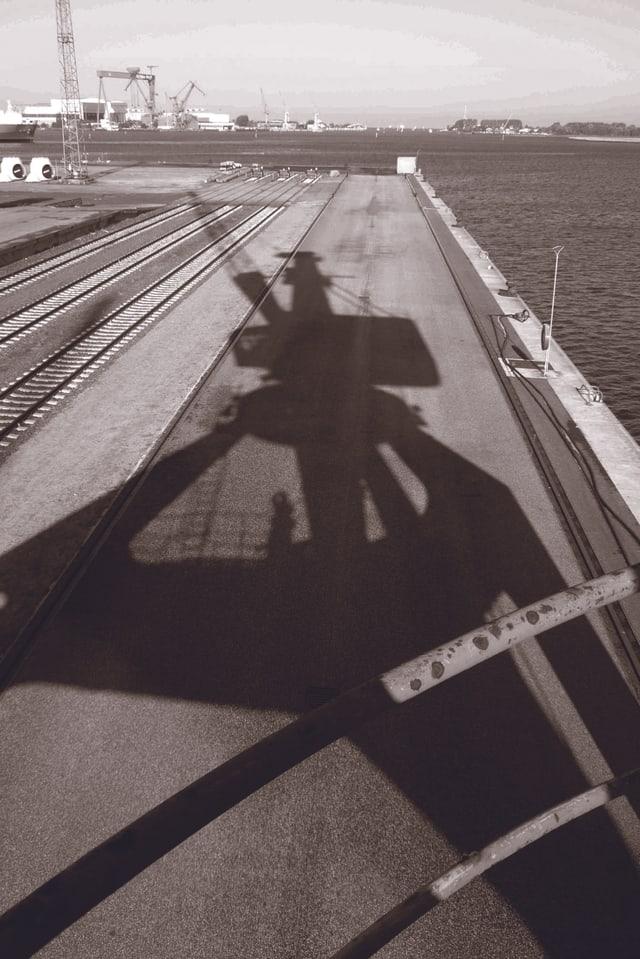 Der Schatten eines Hafenkrans in Schwarz-Weiss, dahinter das Meer.