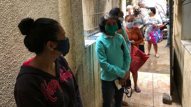 Frauen mit Maske stehen in einer Reihe.