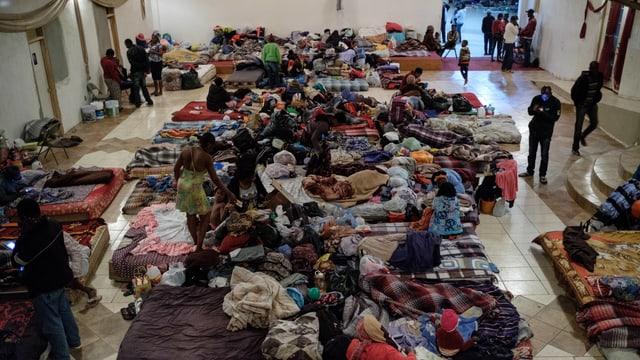 Grosser Saal mit Notbetten und den Habseligkeiten Dutzender Menschen.