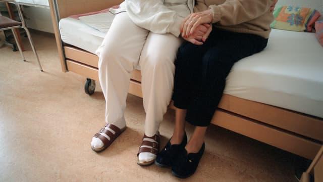 ältere Frau mit Pflegefachfrau auf Bettkante