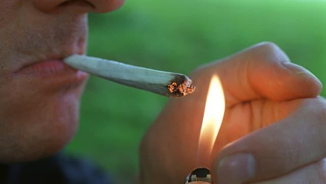 Ein Mann zündet sich einen Joint an.