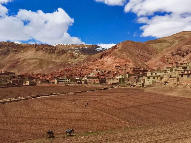 Dorf am Fusse einer Hügelkette.