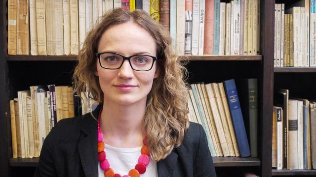 Eine junge Frau steht vor einem Bücherregal.