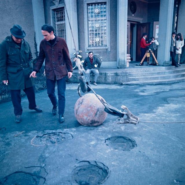 Menschen vor einem Gebäude. Am Boden liegt eine grosse Kugel, die Löcher in den Boden gemacht haben zu scheint.