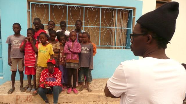 Ein Mann mit Mütze blickt auf eine Gruppe von Kindern.