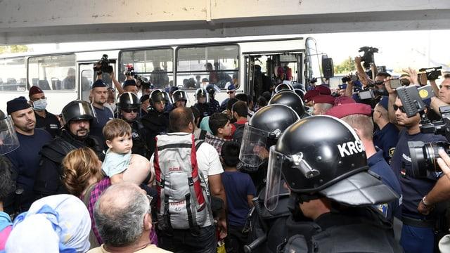 Flüchtlinge werden in einen Bus gelotst.