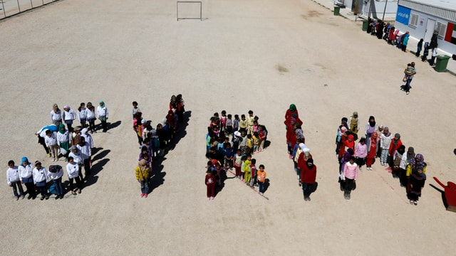 Kinder formen auf einem Platz das Wort SYRIA.