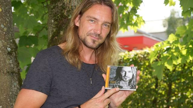Ein Mann mit langen Haaren lehnt sich an einen Baum und hält eine CD in der Hand.