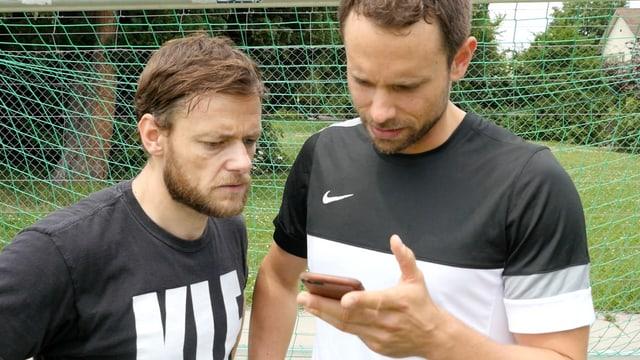 Zwei Männer schauen gebannt auf ein Smartphone.
