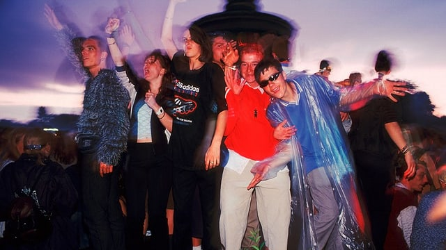 tanzende junge Menschen in bunten Kleidern.
