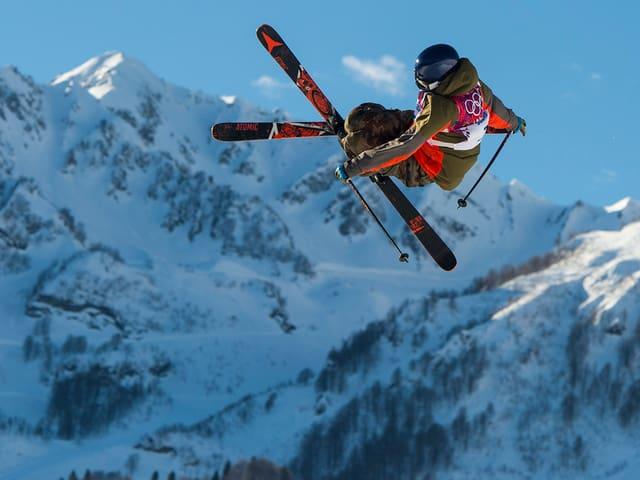 Elias Ambühl aus dem Team Schweiz fliegt über die Schanze vor einer Bergkulisse