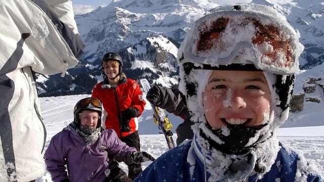 Kinder im Skigebiet blicken in die Kamera.