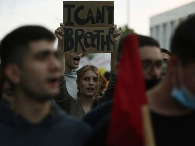 Demonstrierende in Athen – eine Frau hält ein Schild mit der Aufschrift «I can't breathe» hoch.