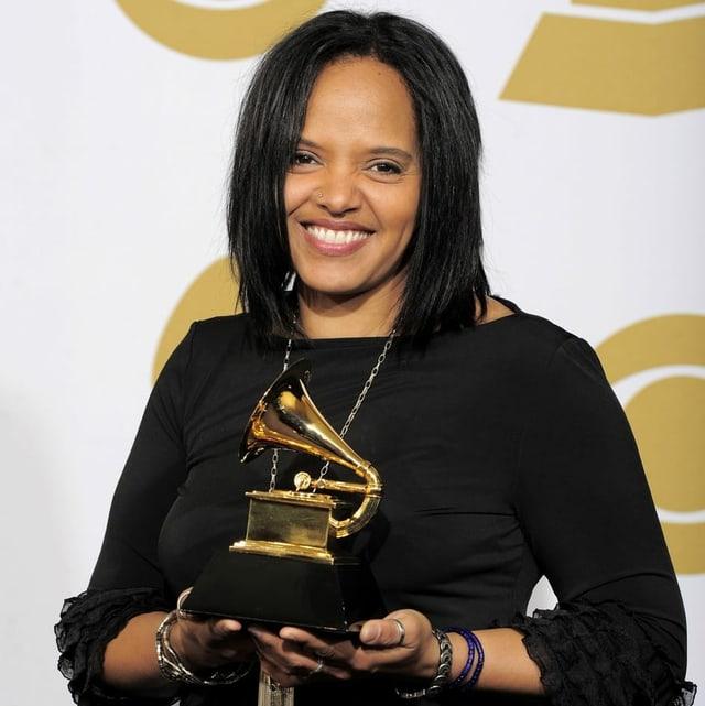 Die Schlagzeugerin Terri Lyne Carrington hält einen Grammy in den Händen.