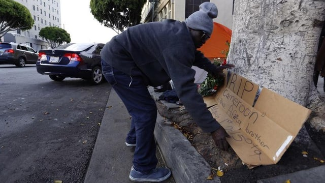 Nach dem Tod des Obdachlosen legt ein Mann ein Gedenkplakat aus Wellkarton am Ort des Geschehens nieder.