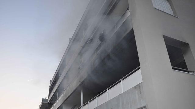 Rauch kommt aus einem Balkon bei einem Wohnblock