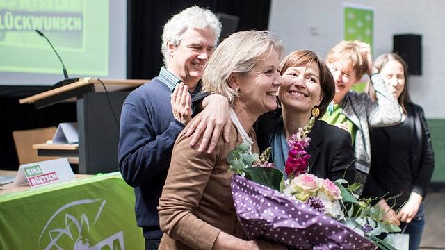 Regula Rytz umarmt Brigit Wyss, die einen Blumenstrauss hält.