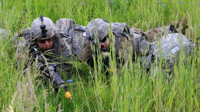 Bewaffnete Soldaten liegen im hohen Gras.