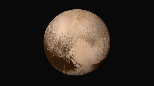 Ein bräunlich-beigefarbenes Bild von Pluto auf schwarzem Hintergrund.