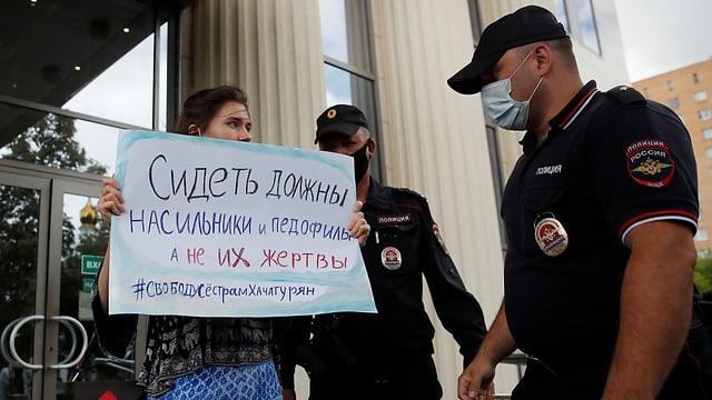 Eine protestierende Frau mit Plakat wird von Polizisten angesprochen.
