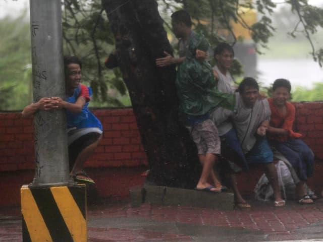 Kinder stehen im Windschatten eines Baumes, ein Junge hält sich an einem Pfosten fest.