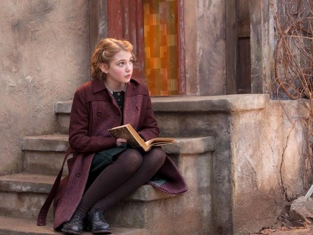 Mädchen sitzt auf Treppenstufen mit einem Buch auf den Knien.