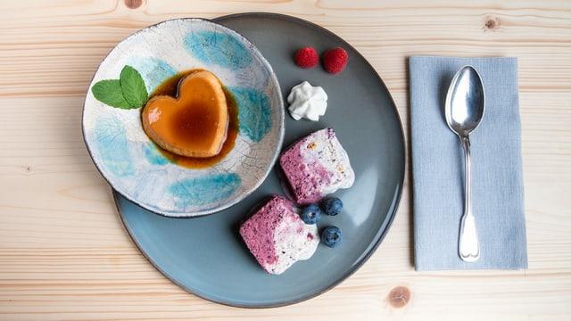 Caramelköpfli und gestrudeltes Vanille-Heidelbeer-Parfait auf blauem Teller