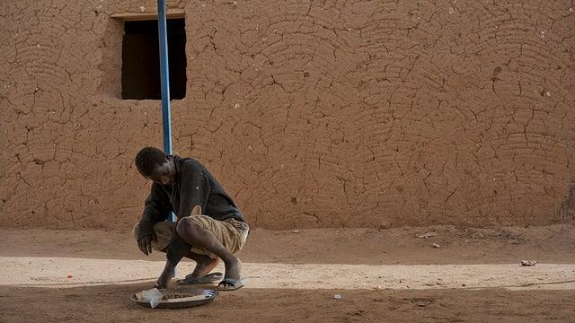 Ein Mann greift nach Essen auf dem Boden, er ist vor einer Sandstein-Mauer mit Fenster, das keine Scheibe enthält.