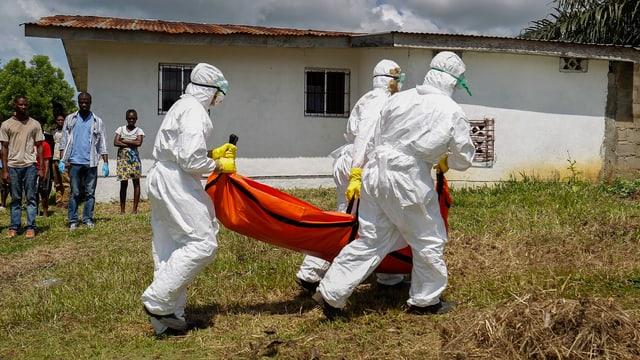 Leiche eines Ebola-Opfers wird von Männern in Schutzanzügen weggetragen