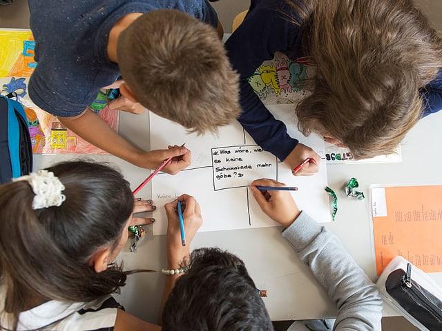 Vier Kinder schreiben auf ein Papier