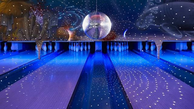 Bowling-Bahnen in blauem Kunstlicht, über der Bahn dreht eine Spiegelkugel